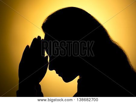 A woman Praying Hands in black background