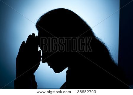 woman meditating with hands on head and black background
