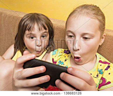 Two little girl using a home mobile phone.