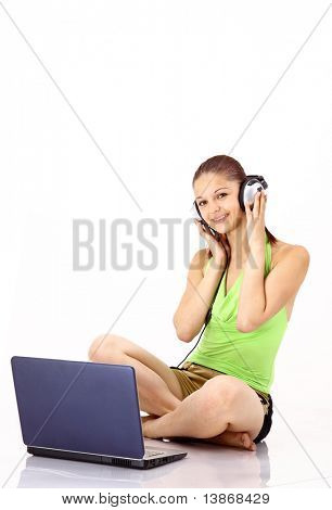 Pretty young girl listening to the music with headphones from her laptop. isolated on white background