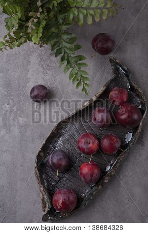 Sweet red plums on the decorative plate