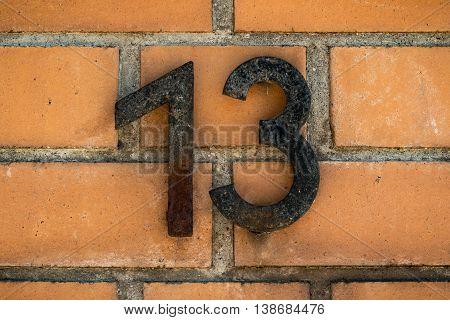 Number thirteen on a orange wall of bricks