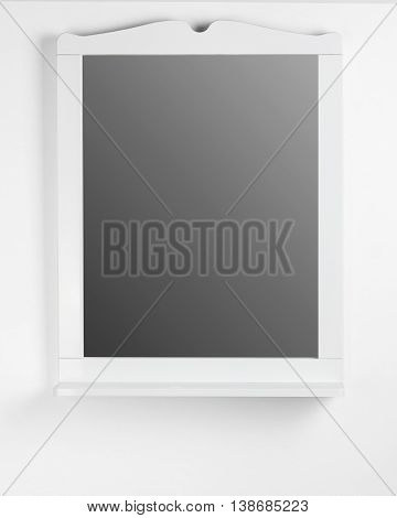 White mirror hanging on a gray wall