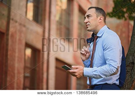 Confident man is having rest outdoors. He is standing and leaning back on tree. Worker is holding mobile phone and looking at building pensively
