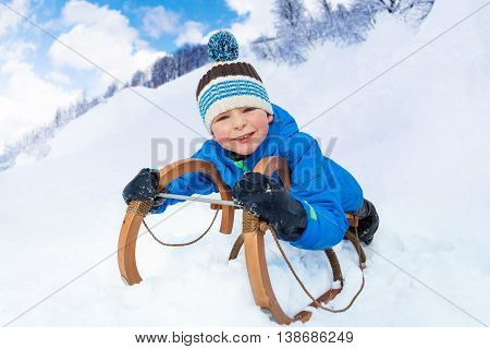 Little boy slide down on sledge smiling and looking at camera