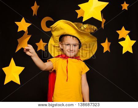 Five years old boy in stargazer costume, standing among paper stars and moon, against black background