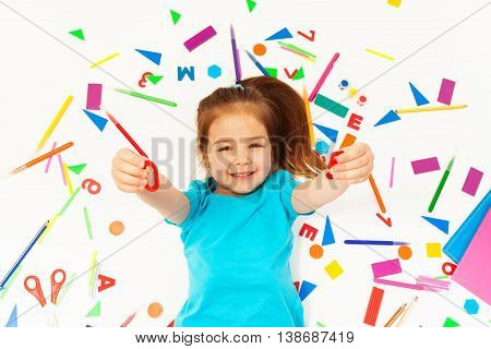 Smiling preschool girl learning mathematics, showing numeral, top view