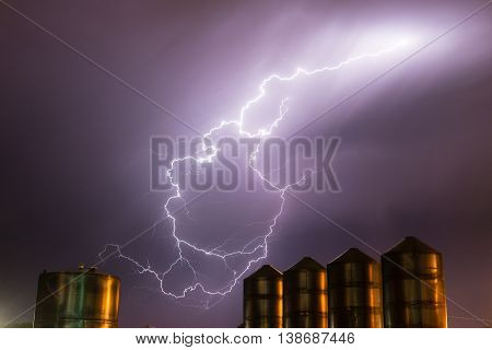 A storm passes over large metal containers releasing electrical charge