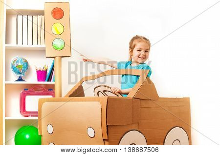 Smiling four years old girl at the wheel of handmade cardboard car pointing to the toy traffic light by her finger