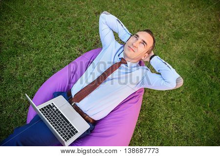 Businessman is relaxing in the nature. He is sitting on air chair with hands behind head. Man is holding laptop