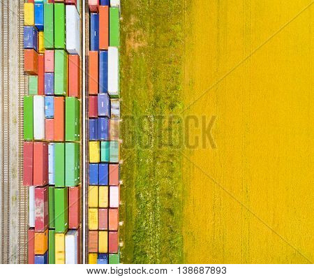Aerial view of containers at railway near wheat field. Industrial background. Industry from above. Environment and transportation. Picture with space for your text.