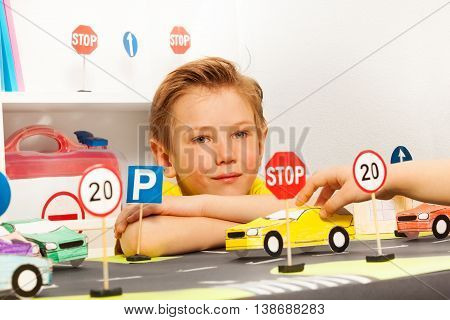 Smart seven years old boy playing driver with toy paper cars and road signs, sitting at the safety road class