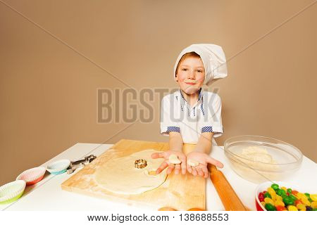 Happy young baker, boy in apron and toque, holding row dough for homemade cookies, background with copy-space