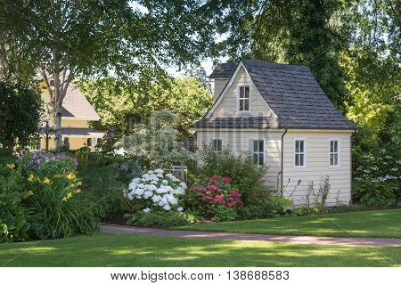 A charming playhouse sits in a shaded perennial garden.