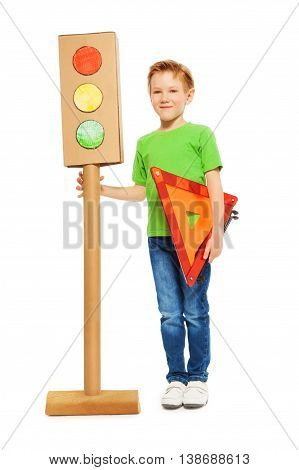 Full-length portrait of seven years old boy, holding warning triangle and cardboard model of light-signal, isolated on white