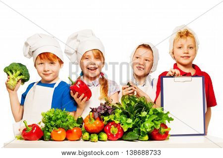 Four smiling cooks, boys and girl with fresh vegetables and blanked clipboard for ingredients list or menu