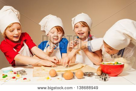 Four smiling bakers, kids in chef's uniform, using cookie cutters to prepare candy filled cookies