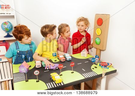Four kids, five years old boys and girl, studying Highway or Traffic Code with handmade cardboard light-signal and road playing field