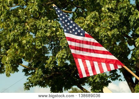United States flag blows in the wind against a blue sky and green trees attached to the wall from the side.