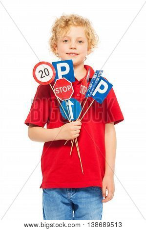 Cute seven years old boy in red t-shirt holding small miniatures of road signs, isolated on white