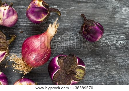 still life with eggplants and onion grown in organic farming on a gray wooden table
