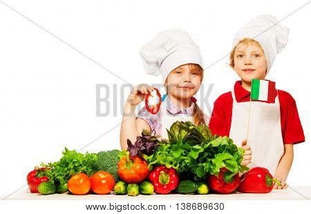 Two happy kids, boy and girl in cook's uniform preparing fresh vegetables, holding Italian flag isolated on white