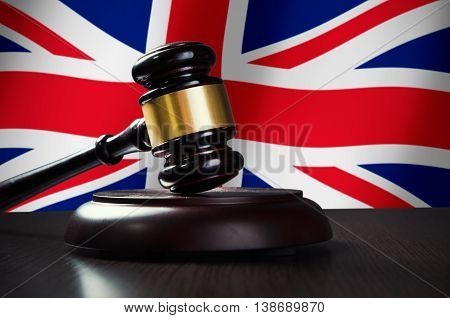 Wooden gavel with United Kingdom flag in background. Justice and law symbol