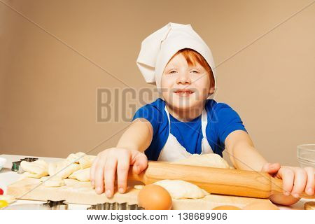 Portrait of redheaded boy in baker's uniform, flattening dough, sitting against background with copy space