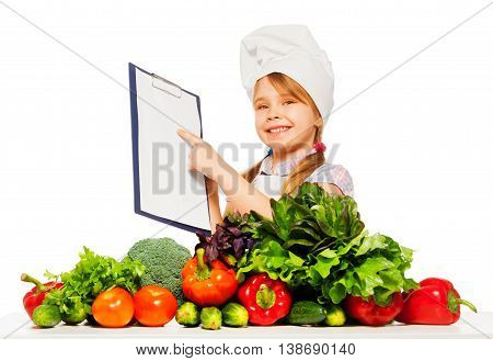 Happy smiling girl in cook's uniform holding blanked clipboard, standing behind the table full of fresh vegetables, isolated on white
