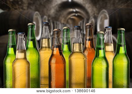 Group Of Cold Wet Beer Bottles In The Cellar With Vintage Kegs
