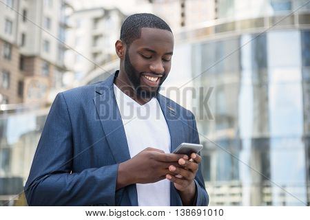 Cheerful young man is typing message on mobile phone. He is standing on street and smiling