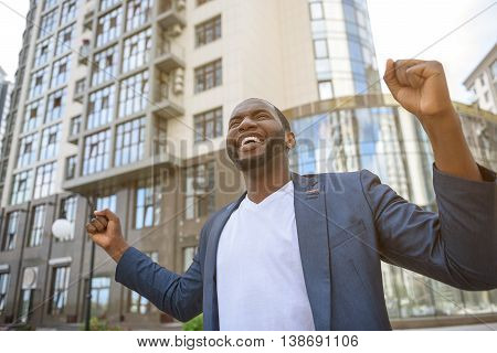 Joyful African businessman is celebrating his success. He is standing and raising fists with triumph. Man is smiling happily