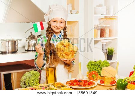 Young chief cook, girl in white apron and hat making pasta, holding small flag of Italy and glass bowl with fettuccine in the kitchen