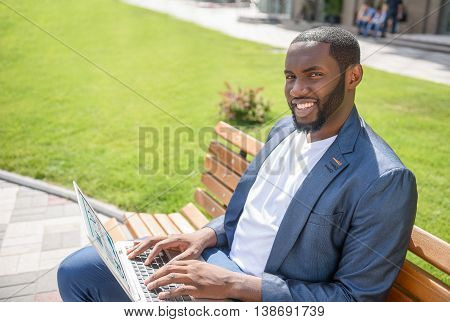 Happy African man is using laptop for work. He is looking at camera and smiling. Worker is sitting on bench in town