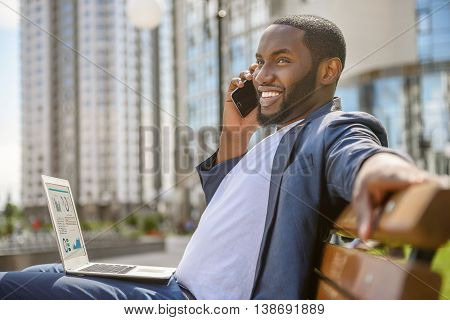 Happy young man is talking on mobile phone outdoors. He is sitting on bench and relaxing. Worker is holding laptop and smiling