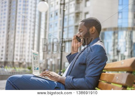 Successful African businessman is using mobile phone and laptop. He is sitting on bench in city and smiling