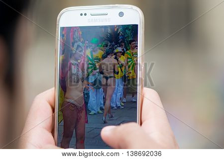 BATH SOMERSET UK - JULY 16 2016 Man photographing bikini dancers on mobile. Bath Carnival procession bringing a South American festival atmosphere to Somerset
