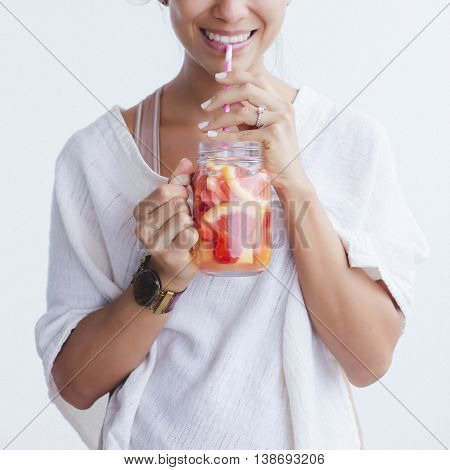 Woman drinking an orange and grapefruit infused water in mason jar.