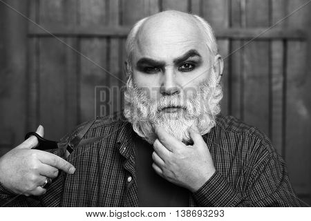 Old Man Cutting Beard With Scissors