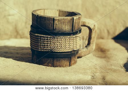 A mug for a nice drink. Close up of wooden mug with thread decor