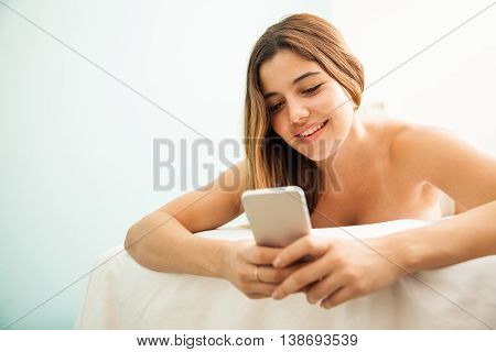 Young Woman With Her Smartphone In A Spa