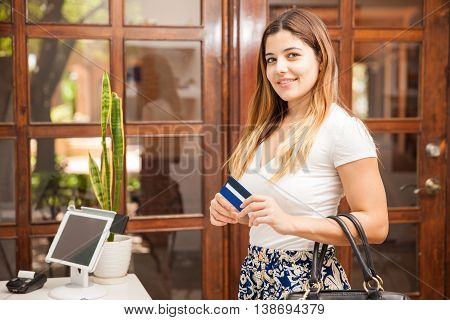Portrait of a beautiful young Hispanic woman using a credit card to pay at a cash register in a spa