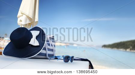 hat on the beach with bag sun glasses and towel