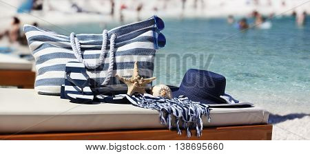 bag with hat sandals starfish sea shell and towel on the beach