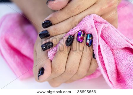 Drying hands girl with stylish manicure pink towel