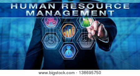 Manager is pushing HUMAN RESOURCE MANAGEMENT on an interactive touch screen. Business metaphor and management concept for workforce planning recruitment career development and compensation.