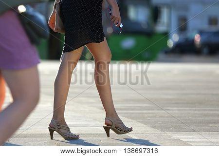 the walking women legs in backlight sunlight