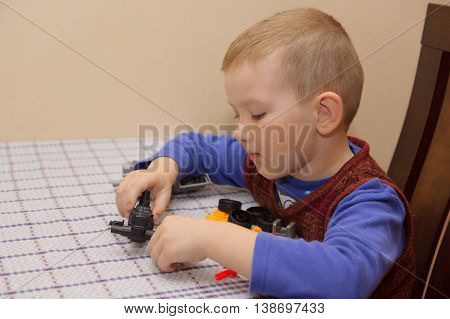 the boy sits at the desktop and assembles the machine from the designer