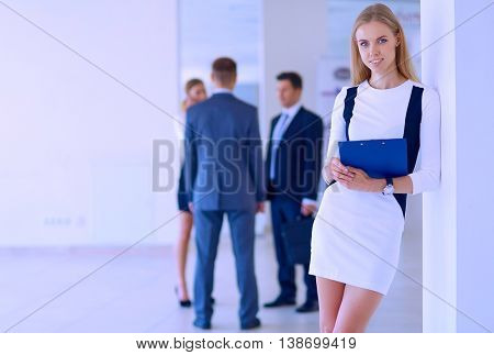 Portrait of young businesswoman in office with colleagues in the background, cool tone