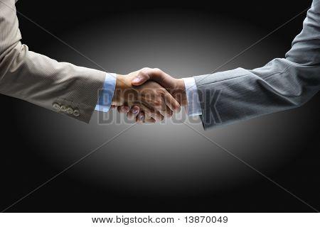 Handshake - Hand halten auf schwarzem Hintergrund